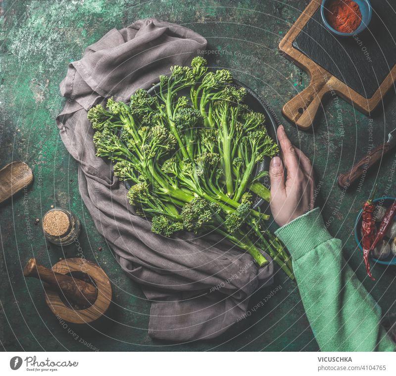 Women hand in green sweatshirt holding wild broccoli on dark rustic background. Top view. Healthy food women top view healthy food preparation kitchen table