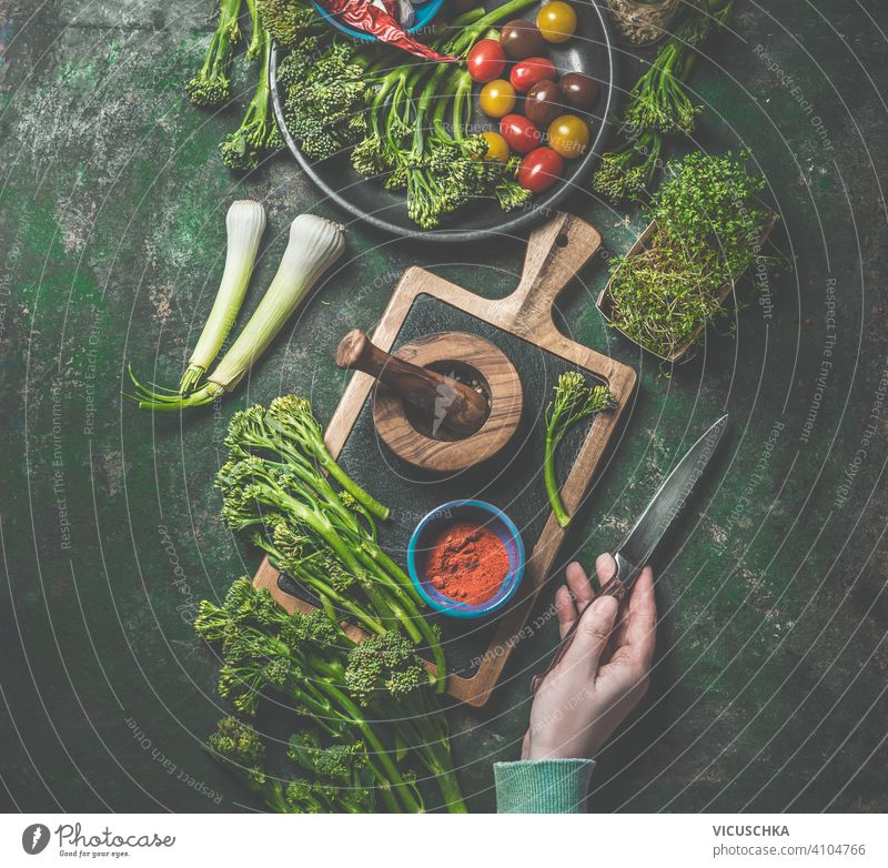 Cooking preparation of wild broccoli. Women hand holding knife on dark rustic background with cutting board and ingredients. Top view. Healthy food cooking