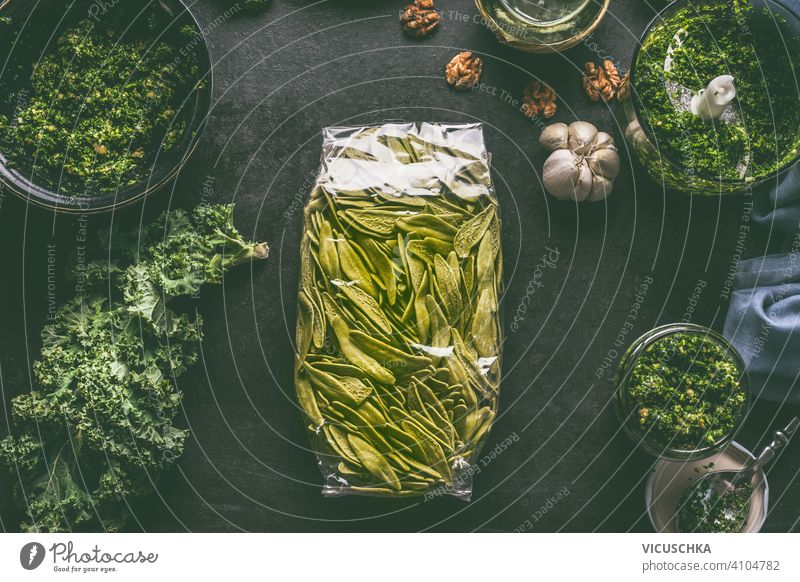 Green pasta in plastic packing on dark kitchen table with kale and other ingredients. Top view green top view rustic brunch noodle nutrition carbohydrate meal