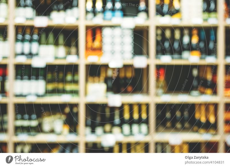 Blurred image of bottles with alcohol on the shelves in supermarket. wine beverage background abstract retail shop store winery rack row shelf blur cellar