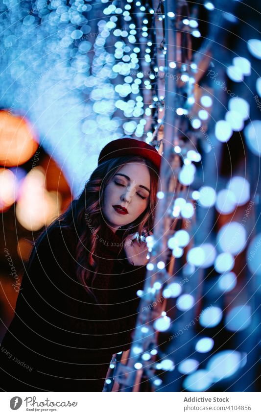 Charming lady in hat enjoying decoration lights at city street woman night christmas amazed wow excited dream casual xmas makeup dark smile laugh touch