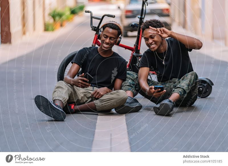 Happy young black male hipsters using smartphones in street friend generation teenager share cool picture cellphone headphone together road asphalt lifestyle