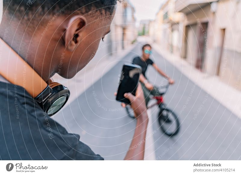 Young black male teenager taking photo on cellphone of friend in street take photo men bmx smartphone cool bike using picture social media communication shot