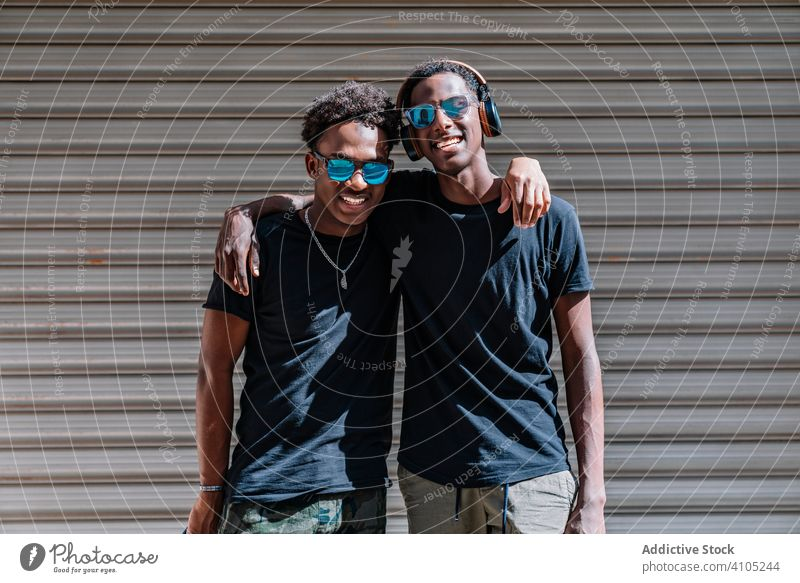 Cheerful young black male friends hugging in street men teenager enjoy cool pastime together friendship hipster lifestyle african american fun carefree freedom