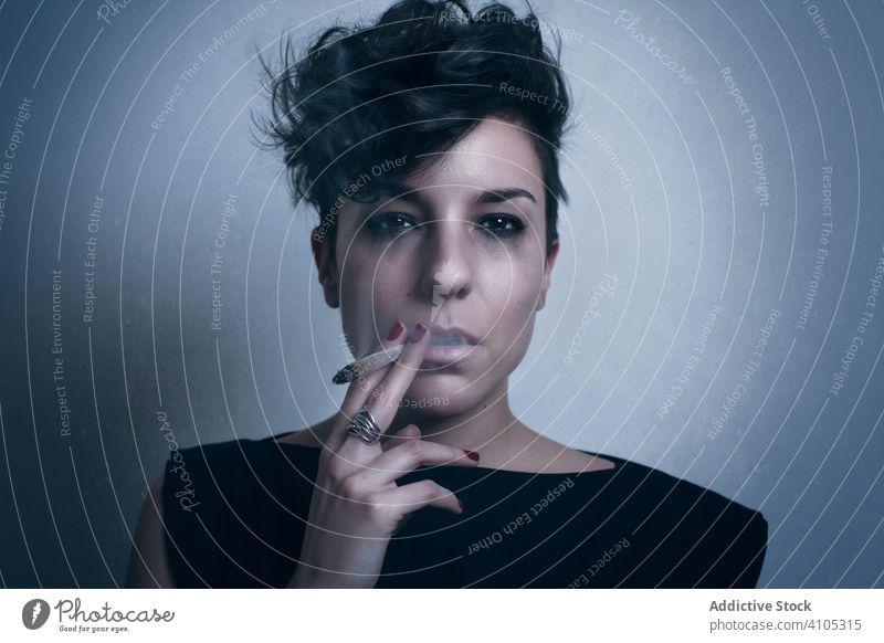 Upset woman smoking cigarette in studio smoke crying unhappy addiction lifestyle habit female joint weed blunt marijuana dope nicotine dependence model drug