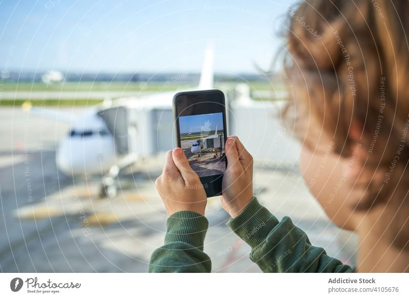 Anonymous child taking photo of airplane in airport take photo smartphone window modern shoot travel passenger kid aircraft trip transport lifestyle capture