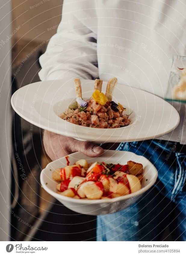 Restaurant waiter carrying a serving of spicy Spanish potatoes and a serving of salmon tartare local food cuisine local cuisine gastronomy snack eating