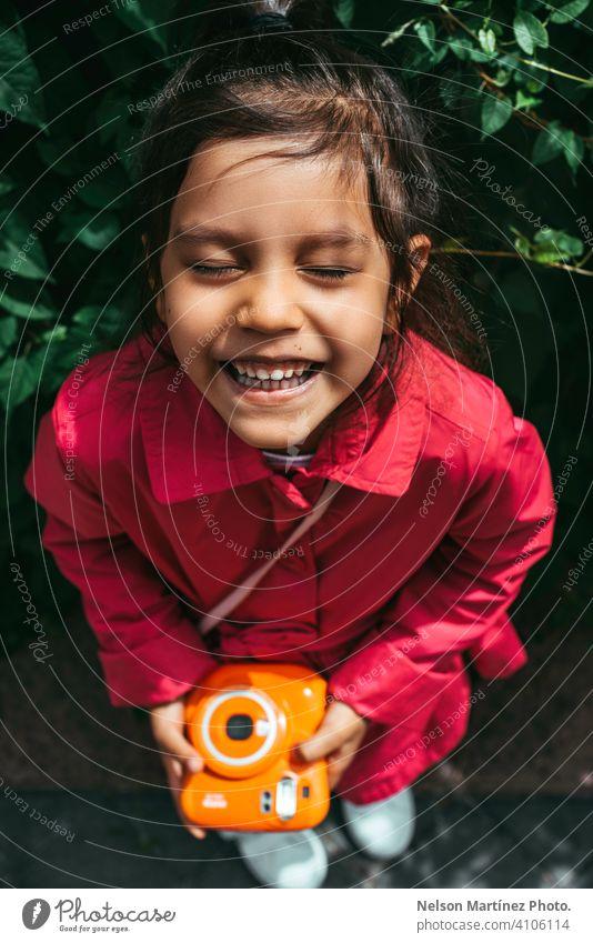 Portrait of a little hispanic girl, wearing a fucsia coat, holding a vintage orange camera childhood people joy amusement holiday playing enjoyment children