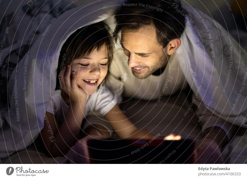Father and son using digital tablet together at night in bed bedtime lying down reading bedroom under blanket storytelling internet online cute evening sleeping