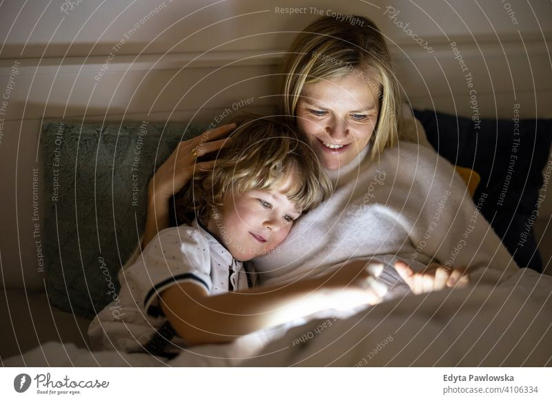 Mother and son using digital tablet together at night in bed bedtime lying down reading bedroom storytelling internet online cute evening sleeping resting boy