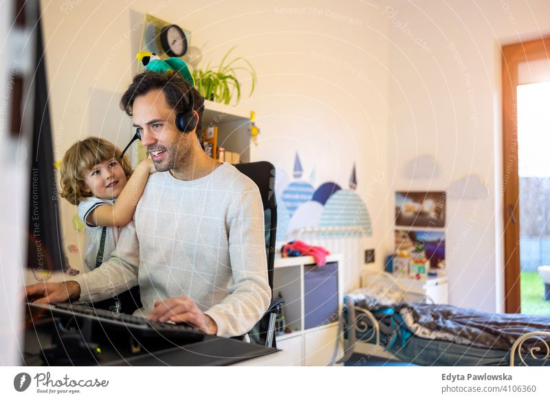 Young man working from home with his little son as a company single father working at home computer busy laptop life balance coronavirus covid social distancing
