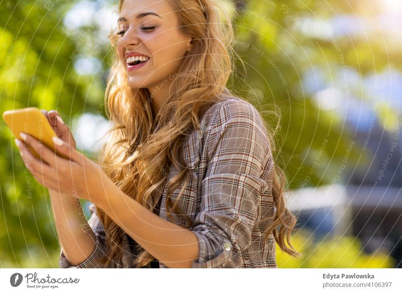 Attractive young woman using smartphone in the city summer girl people young adult female lifestyle outdoors millennial outside attractive beautiful positive