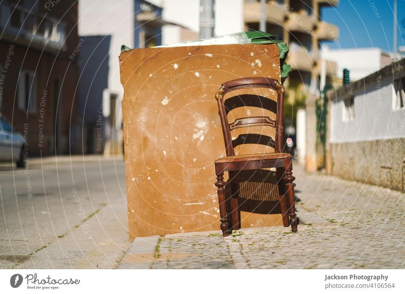Vintage wooden chair next to trash bin on the public street rubbish outdoor dirty spotted painted faro portugal sunny art abandoned neglected dustbin trash can