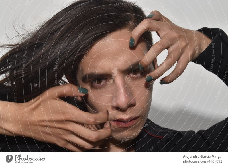 Handsome young man with long brown hair, green painted nails, with penetrating gaze and serious expression, fixed gaze close up attractive beauty
