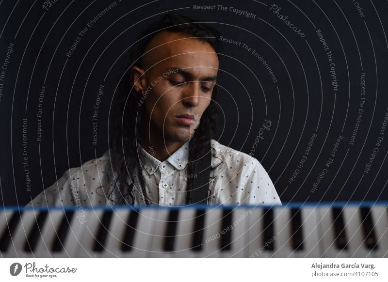 Conceptual music photography, keys of piano in the foreground with a long haired man musician in the background with a peaceful expression, black background