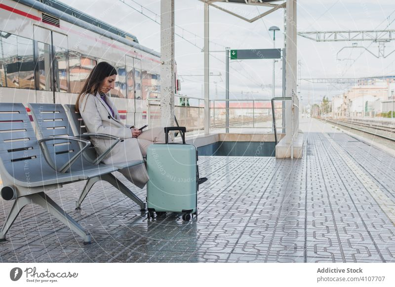 Woman waiting for train and using phone woman station mobile phone travel smartphone holiday suitcase railway bench young transport terminal transportation trip