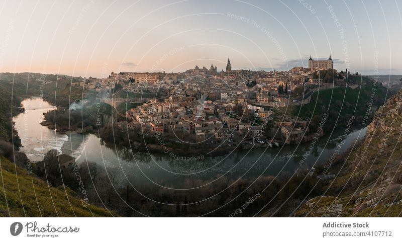 Old town across river at sunset time architecture old medieval cityscape travel tourism building scenic hill water destination picturesque spain toledo