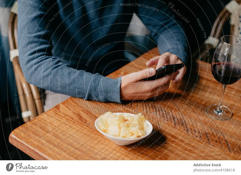 Man using smartphone in cafe man table wine drink rest relax male beverage restaurant casual device gadget surfing modern lifestyle mobile social media browsing