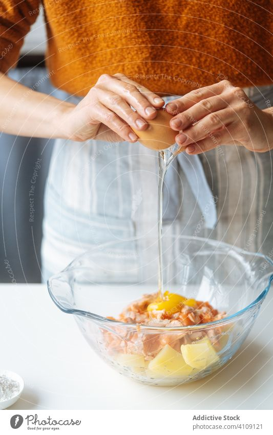 Woman adding egg into bowl with food ingredients break cooking mix stuffing woman recipe fish salmon potato kitchen glass transparent healthy meal female