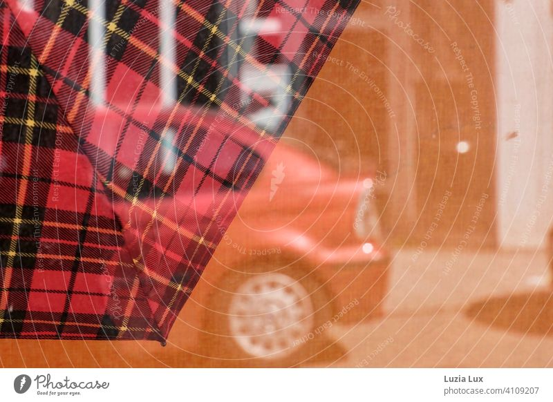 A checkered umbrella in the shop window, a parked red car reflected in the sunlight. Shop window Umbrella Sunlight Street Red Orange Reflection Day Town