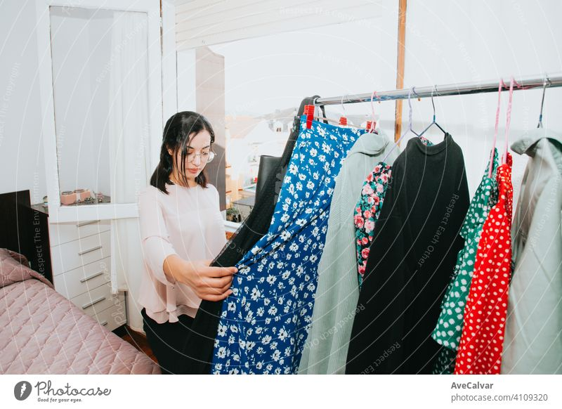 Young arab woman checking his clothes at home during a super bright day, retail and resell concept young selling clothing shopper owner customer fashion buying