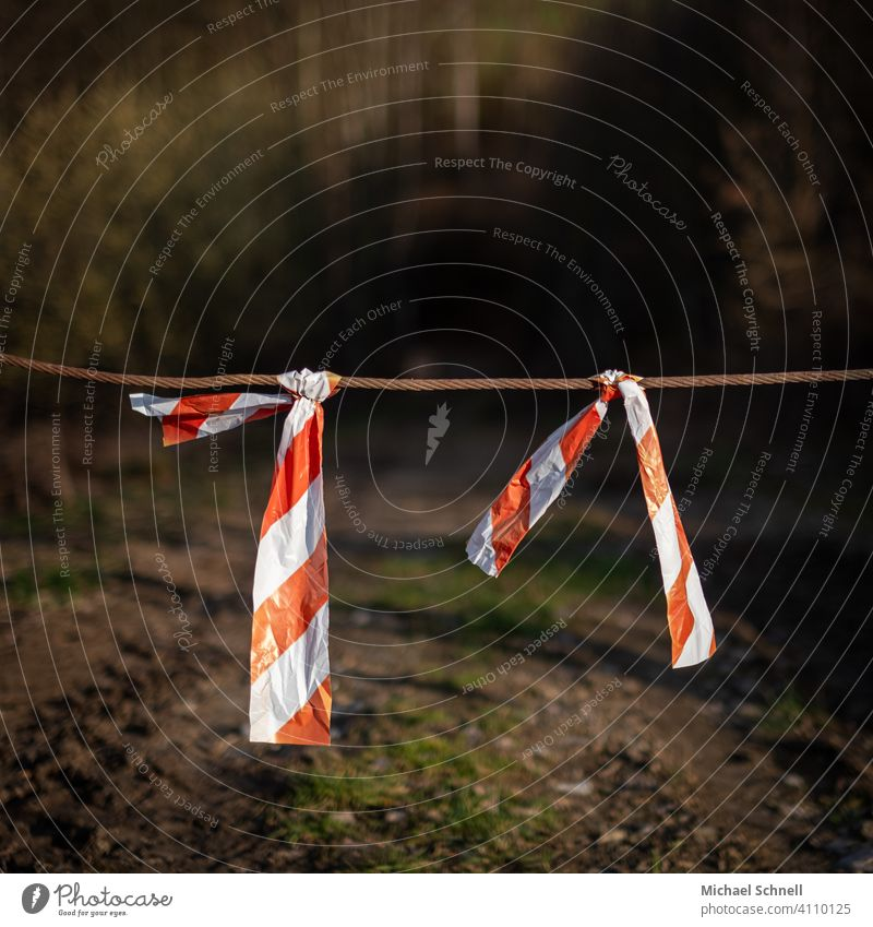 cordon barrier tape No through road Transit prohibited Barred Reddish white forest path passage Passage blocked Safety cordoned off Exterior shot Deserted