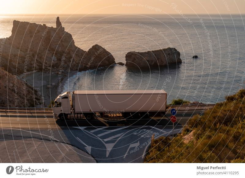 Truck with refrigerated semi-trailer driving on a road next to a beach. Camion Refrigerado Montaña Colour photo Deserted Nature Blue Carretera Playa Mar Islote