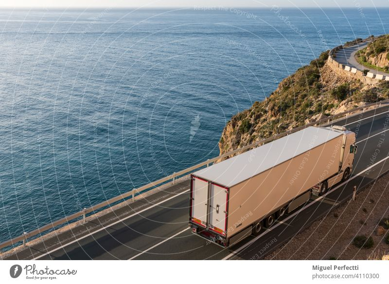 Truck with refrigerated semi-trailer driving on a road by the sea. Camion Refigerado Temperature controller Logistica Transporte Transportar Paisaje Mar Azul