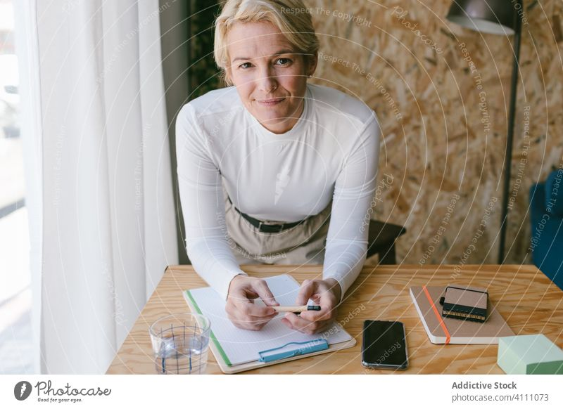 Blond woman writing on clipboard bending on office desk businesswoman note plan write pensive workplace table concentrate information document job smart