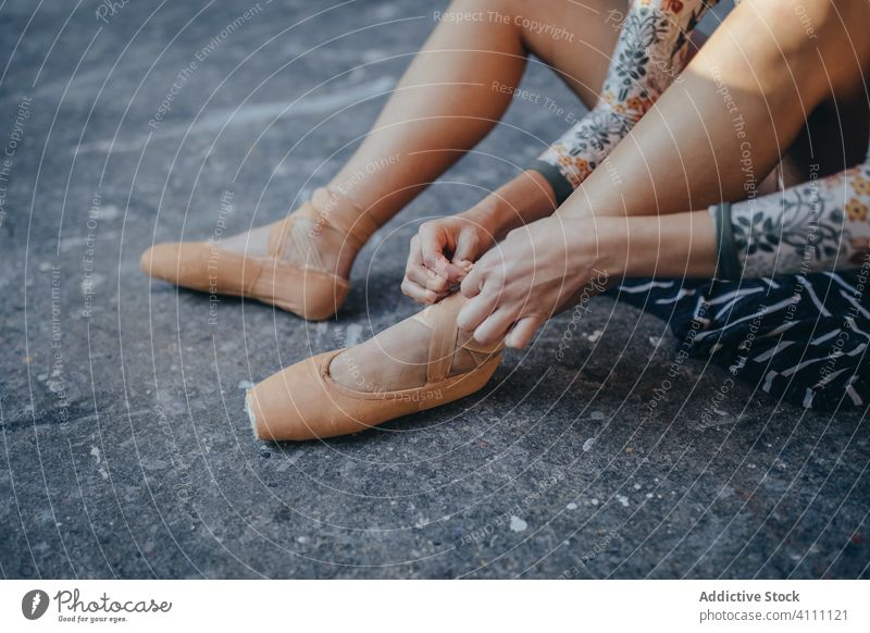 Woman sitting on floor and putting on ballet shoes ballerina pointe put on woman classic dancer choreography prepare female elegant footwear activity practice
