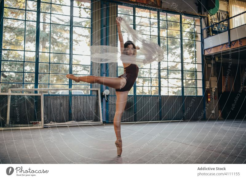 Young woman in bodysuit dancing with veil in studio dance grace light rehearsal romantic ballerina elegant flexible slim choreography alone motion tulle young