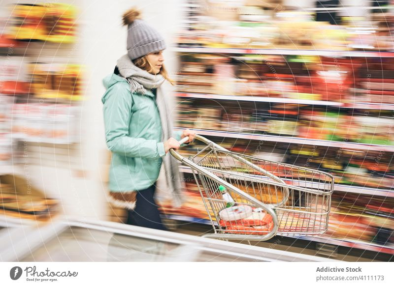 Woman choosing purchases in supermarket woman store cart food shopper customer buy grocery defocused motion retail product trolley choose commerce choice buyer