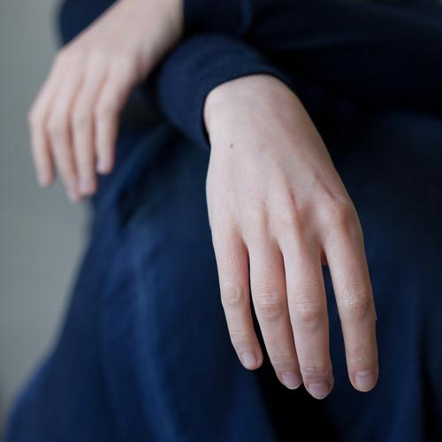 Relaxed Human being Feminine Woman Adults Hand Fingers 1 30 - 45 years Fashion Jeans Sweater Relaxation Crouch Sit Esthetic Simple Natural Blue Contentment
