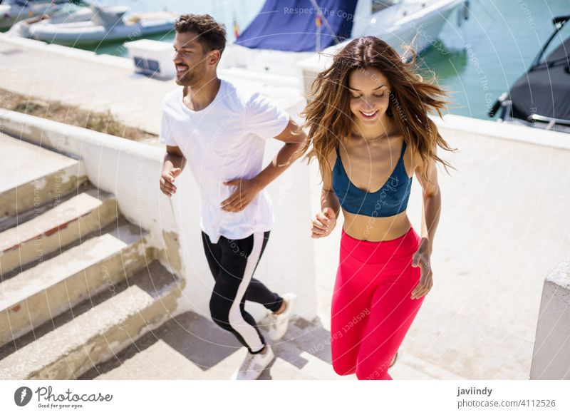 Athletic couple training hard by running up stairs together outdoors. fitness step workout sport woman girl female activity young leisure jogger caucasian