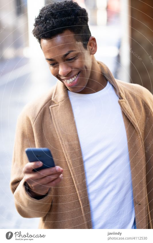 Young black man using his smartphone outdoors. male cuban young person smiling happy student casual lifestyle t-shirt adult guy african portrait cellphone