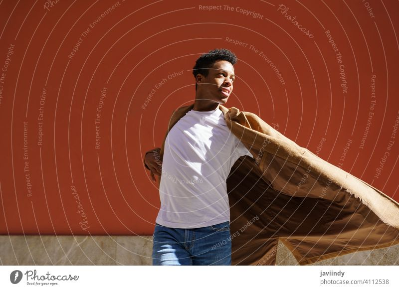Young black man dancing on red urban wall. street happiness male cuban young expression person happy looking dancer outdoor one joy casual lifestyle adult guy