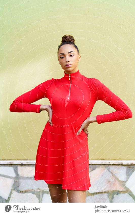 Young black woman in red dress with a serious expression in urban background. bow hairstyle model beauty fashion pretty portrait girl young female person lady
