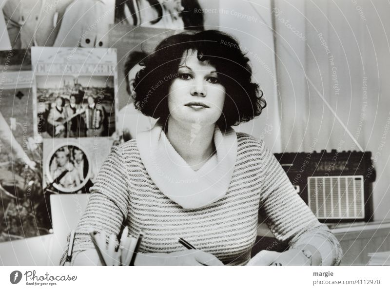 A young woman sits at her desk in the office and looks into the camera. Behind her is an old radio. Artist photos hang on the wall. Woman Young woman