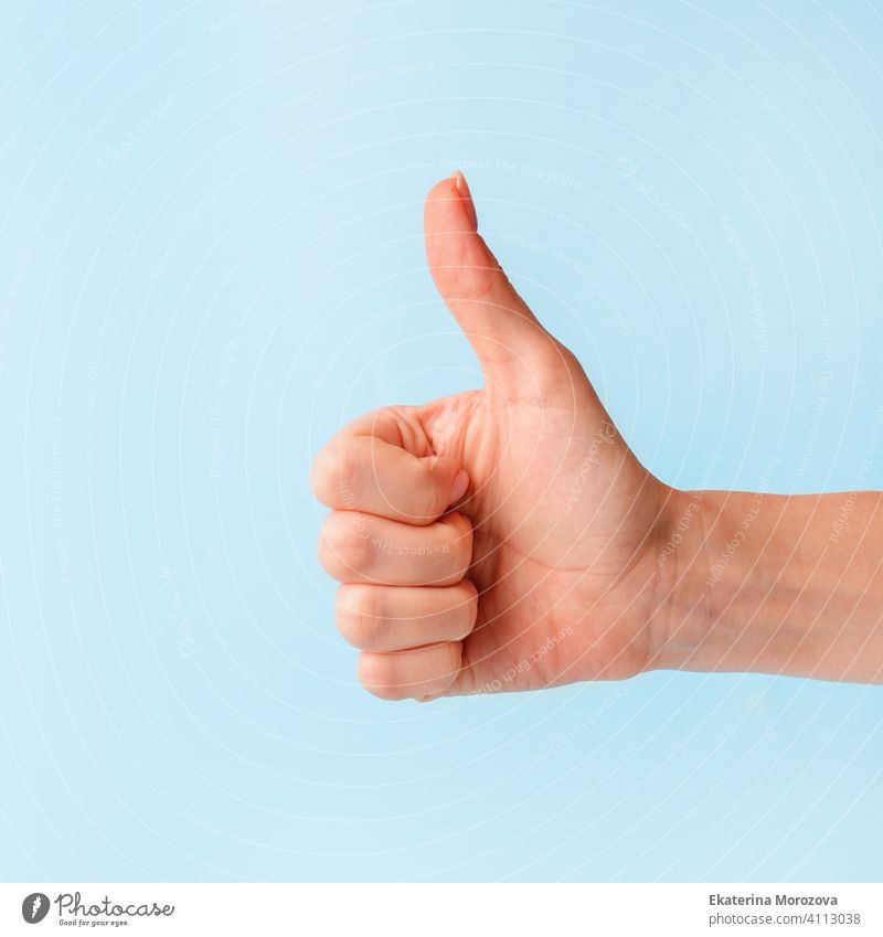 Closeup of female hand showing thumbs up sign against pastel blue background, copy space, minimal concept woman finger symbol business arm good person positive