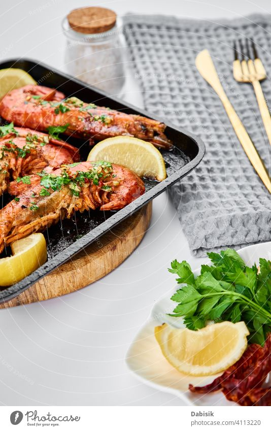 Grilled large queen shrimps with lemon and spices on the grill pan prawns seafood red background dark black shellfish dish tiger cooked crayfish eating gourmet