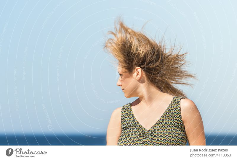 Portrait of a middle-aged blonde caucasian woman in a green dress and hair shaking in the wind sea summer sun relax outdoor female lady sunny alone outside