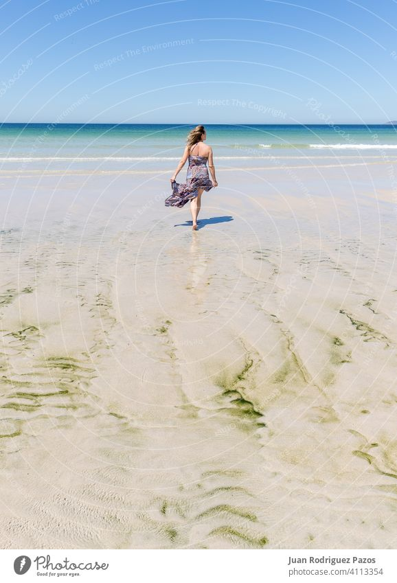 Middle-aged blonde caucasian woman in a dress walking on the beach sea summer sand relax outdoor female lady paradise quiet relaxation relaxing solitude sunny