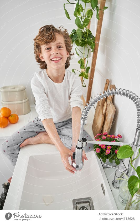 Blond child washing his hands in the kitchen sink to prevent any infection lifestyle kid indoors son boy water home young hygiene domestic childhood folding