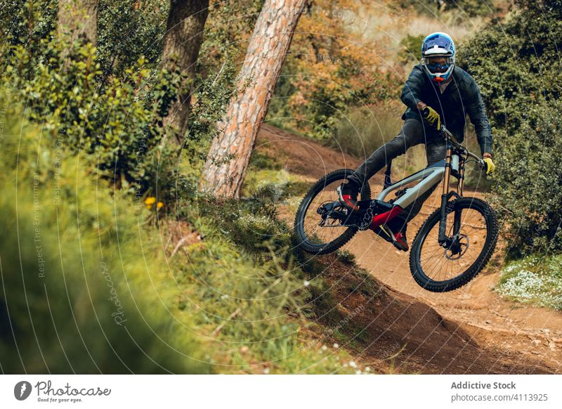 Downhill rider jumping downhill bike and doing whip trick mountain biking trail nature mtb equipment speed cycle professional lifestyle fit fun sport cyclist