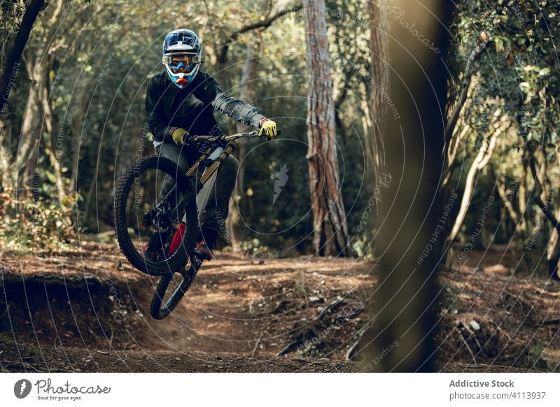 Biker in jeans and plaid shirt jumping bike down MTB trail downhill adventure professional mountain bicycle sport rider outdoor landscape man track biking