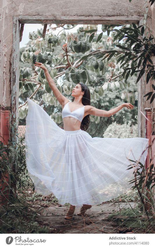Graceful lady dancing in garden woman dance ballet grace concept young slim arch bush female skirt bra outstretch elegant ballerina perform dancer move flexible