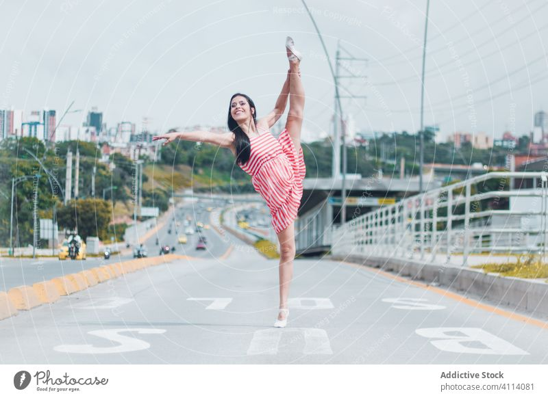 Happy woman dancing on road dance ballet grace concept outskirts split smile young female slim elegant ballerina perform city traffic modern dancer move