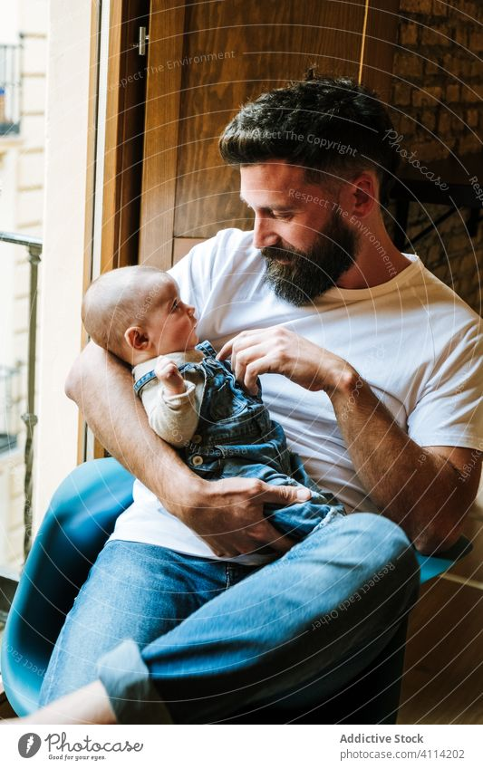 Bearded father communicating with baby communicate hug home love tender window sit cozy chair man infant kid child little embrace parent cuddle close