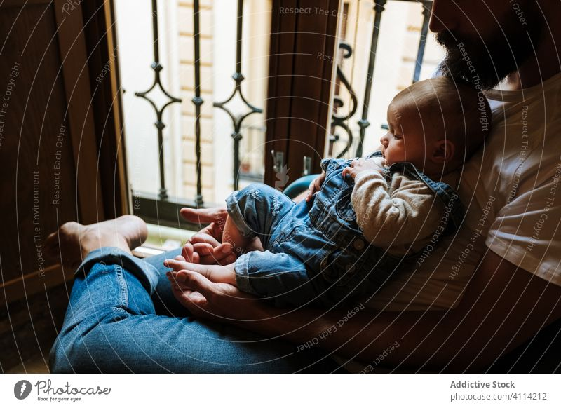 Bearded father with baby sitting near window beard communicate hug home love tender cozy chair man infant kid child little embrace parent cuddle close