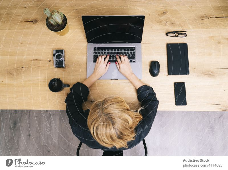 Woman working from her studio office at home. computer technology business desk workplace woman coffee laptop view internet using education cup phone wooden mug